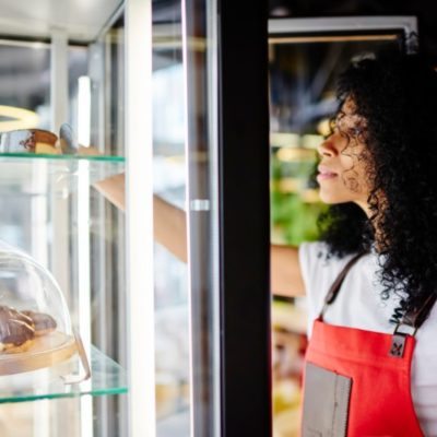 woman taking out a cake from a display refrigerator in a cafe